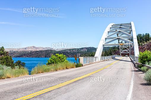 Road with Flaming Gorge Reservoir Bridge with white color and lake river with blue color