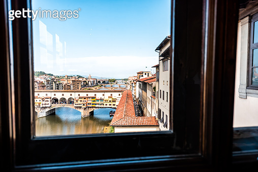 Florence, Italy Firenze high angle view orange colorful buildings and Arno river during summer morning sunrise in Tuscany with Ponte Vecchio through window