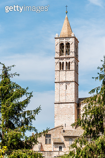 Assisi, Italy town or village city in Umbria with Basilica di Santa Chiara Saint Clare church bell towen during sunny summer day vertical view