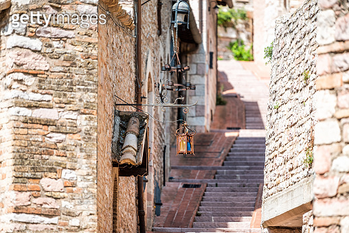 Assisi Umbria Italy empty narrow stone street with nobody in small historic medieval town village during summer day architecture with steps up and lantern