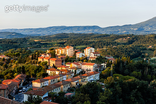 Chiusi village cityscape at sunrise in Umbria Italy with rooftop houses on mountain countryside and rolling hills