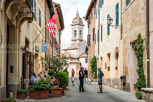 Street in small historic medieval town village in Tuscany and famous church bell tower