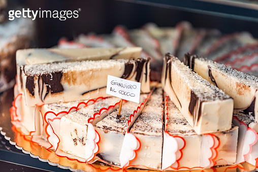 Closeup of chocolate coconut cream cheese cheesecakes swirl slices dessert on tray window display in gourmet bakery Italian cafe with sign