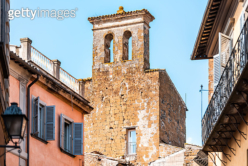 Orvieto, Italy Italian outdoor empty street in Umbria historic city town village road narrow alley with orange walls church bell tower old abandoned ruin closeup