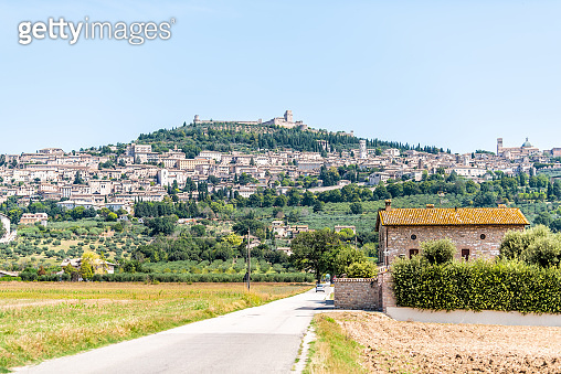 Road leading to village city of Assisi in Umbria, Italy cityscape of church during sunny summer day farm rural landscape Etruscan countryside