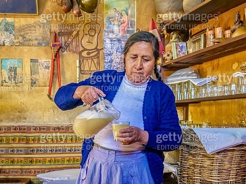 A Peruvian woman pours chicha from a pitcher into a glass in a local chicheria.