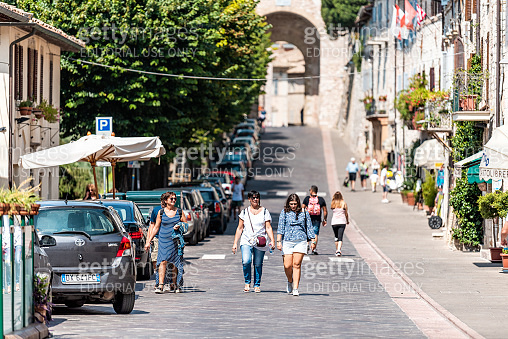 City in Umbria with tourists people walking on street road during sunny summer day in historic St Francis town village