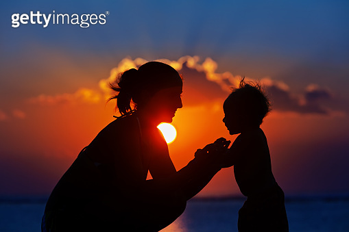 Black silhouette of mother, baby son walk by sea beach