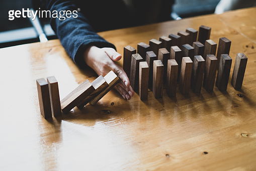Alternative risk plan and strategy in business businesswoman hand stopping falling wooden dominoes effect business success concept