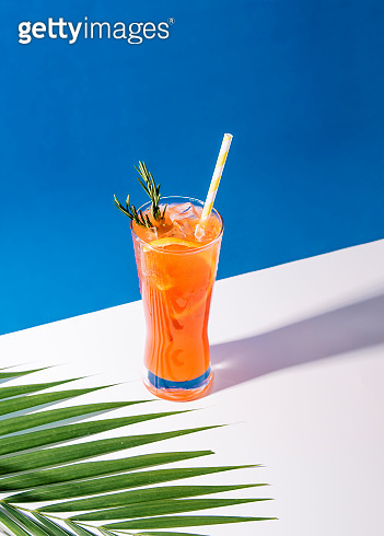 Cold and refreshing orange punch cocktail with orange slice on blue background. summer drink.