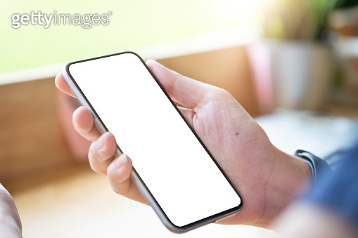 Mockup image of woman's hands holding mobile phone with blank screen in modern cafe