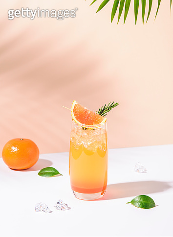 Cold and refreshing orange punch cocktail with orange slice on color background. summer drink.