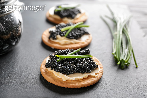 Cookies with delicious black caviar on slate plate, closeup