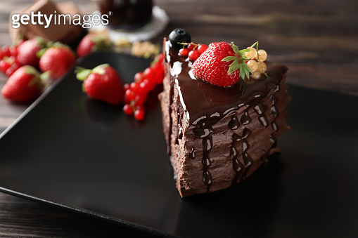 Plate with piece of tasty chocolate cake and berries on plate