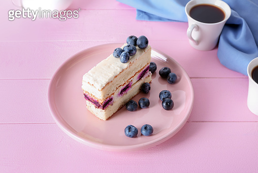 Plate with piece of delicious blueberry cake on color wooden table