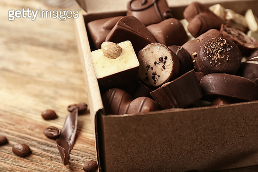 Box with yummy chocolate candies on wooden table
