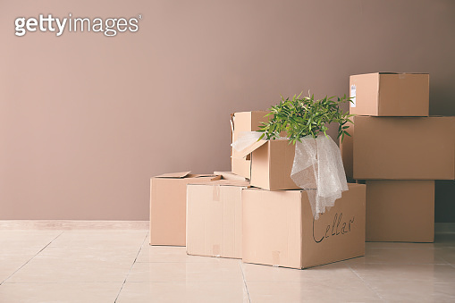 Packed carton boxes on floor near wall. Moving house concept