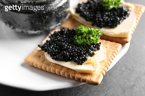Cookies with delicious black caviar on plate, closeup
