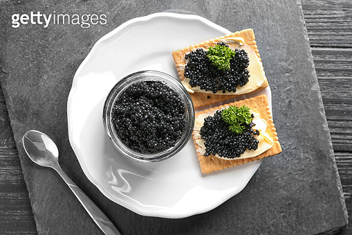 Jar and cookies with delicious black caviar on plate