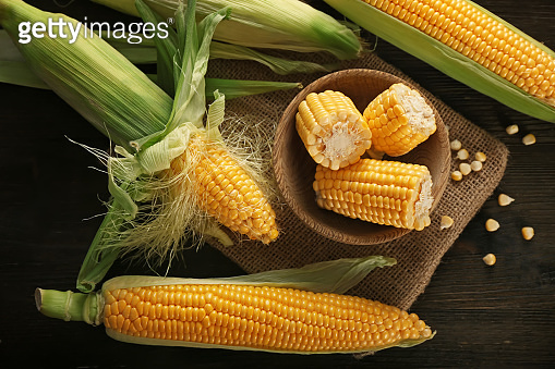 Bowl with fresh corn cobs on wooden table