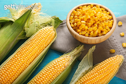Bowl with corn kernels and cobs on color table