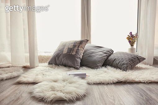 Cozy place for rest with soft pillows and furry rugs near window