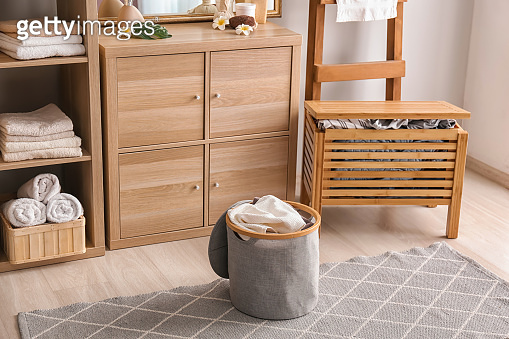 Laundry basket with dirty towels on floor in bathroom