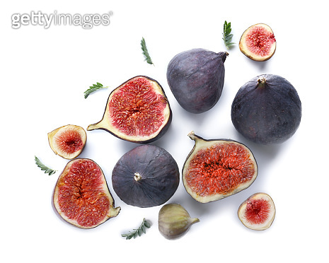 Whole and cut ripe figs on white background