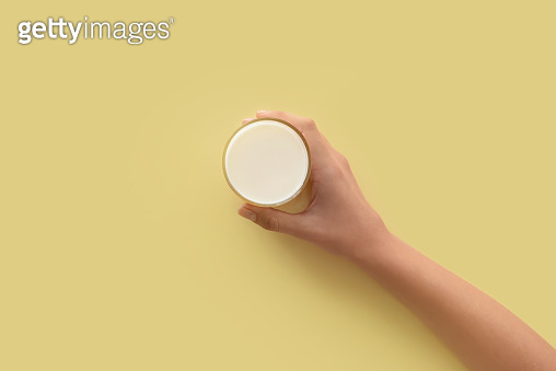 Female hand holding glass of milk on color background