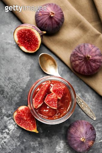 Jar of tasty fig jam on grey table