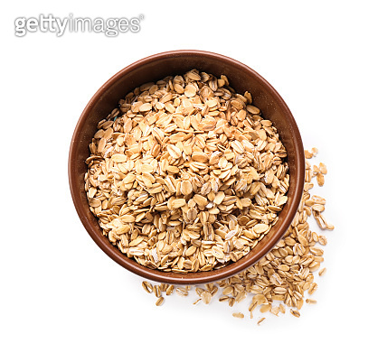 Bowl with raw oatmeal on white background