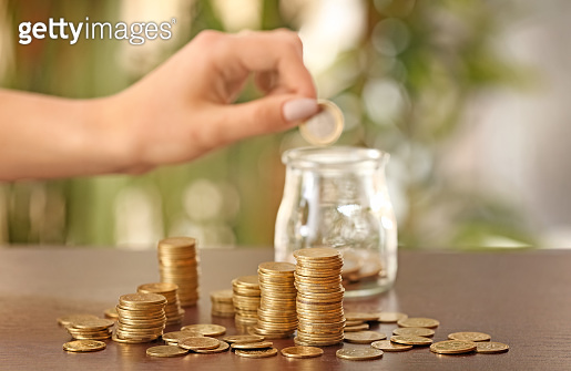 Woman putting coins into glass jar on table. Savings concept