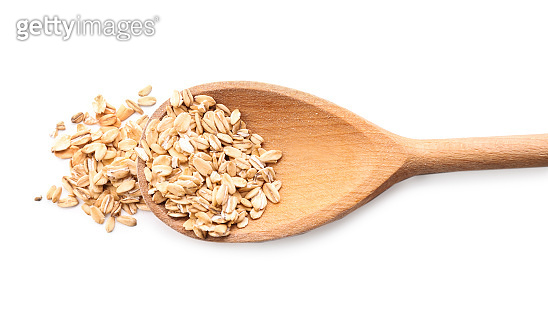 Spoon with raw oatmeal on white background