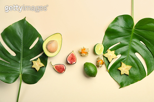 Summer composition with fresh monstera leaves and fruits on light background