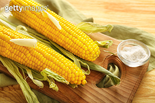Board with tasty corn cobs, butter and salt on wooden table
