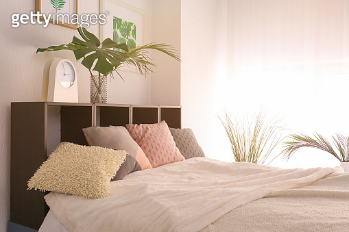 Comfortable bedroom with green tropical leaves