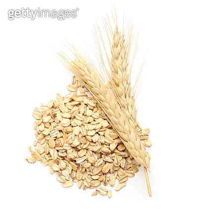 Heap of raw oatmeal and spikelets on white background