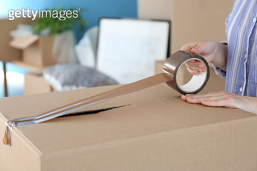 Woman packing carton box indoors. Moving house concept