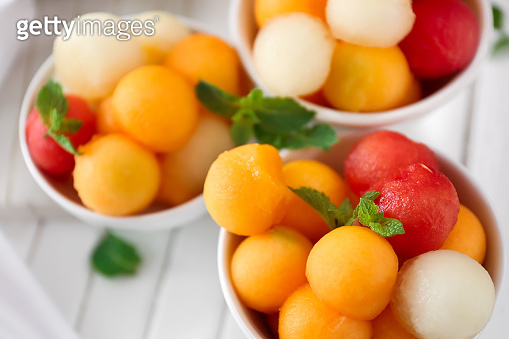 Bowls with tasty melon dessert on table, closeup