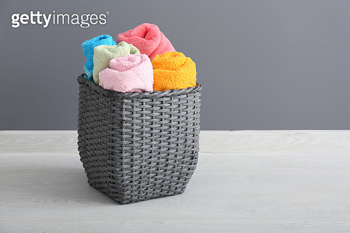 Laundry basket with clean towels on floor near grey wall