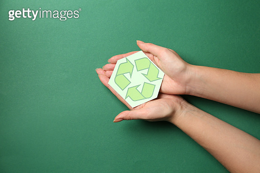 Female hands with recycling symbol on color background