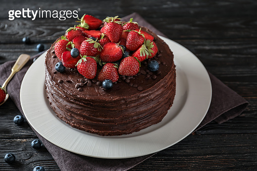 Tasty chocolate cake decorated with strawberry and blueberry on wooden table