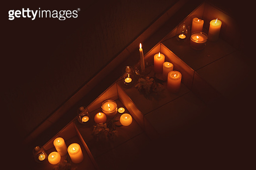 Burning wax candles on stairs in darkness