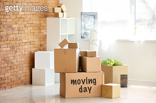Carton boxes and interior items in room. Moving house concept