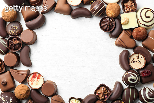 Frame made of different tasty chocolate candies on white wooden background