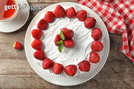 Delicious cake with strawberries on wooden table