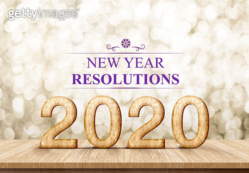 2020 happy new year rosolutions (3d rendering) on wood table with sparkling gold bokeh wall,leave space for display or montage of design or content.