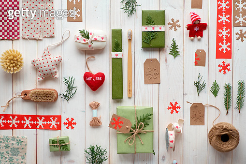 Various Christmas or New Year winter holiday eco friendly decorations, craft paper packages and eco friendly gift ideas. Geometric flat lay with gift boxes decorated with ribbon, cord and evergreens