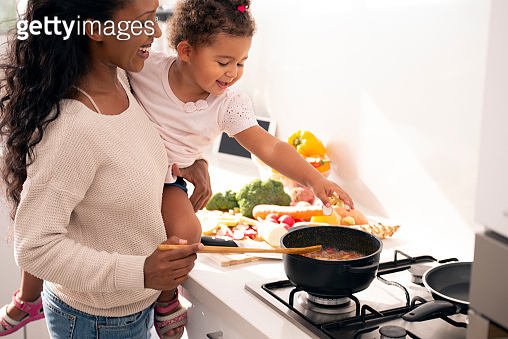 Mother and daughter cooking a soup.