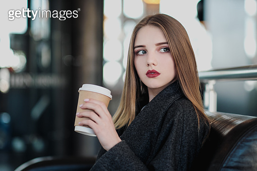 A young beautiful brunette girl in a gray coat is sitting on a bench waiting. Drinking coffee and holding a paper cup with a drink.